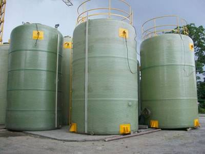 There are several FRP chemical storage tank with yellow ladders.