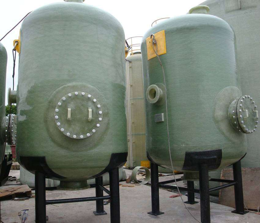 There are two FRP chemical storage vessels with black four-leg supports.