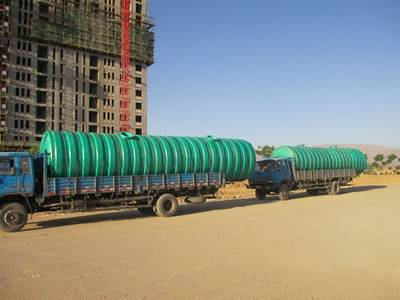 Two threaded FRP septic tanks are delivered to worksite.