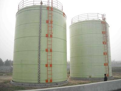 There are two vertical FRP tanks with orange ladders.